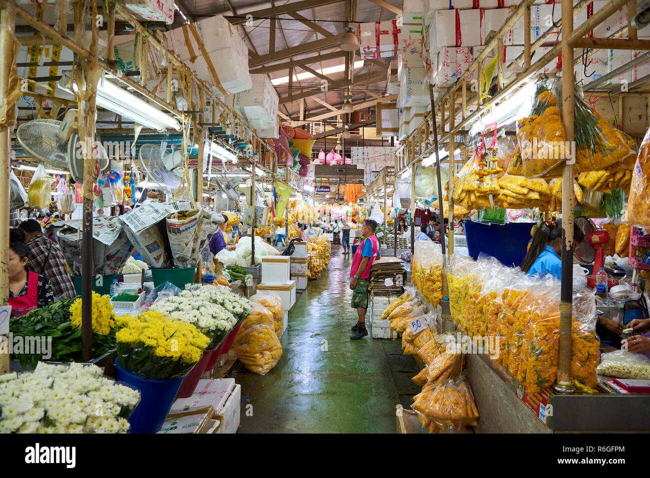 Famous Bangkok flower market. This is one of the many corridors in the covered market, lined with stalls selling wholesale petals used for decorative  Stock Photo