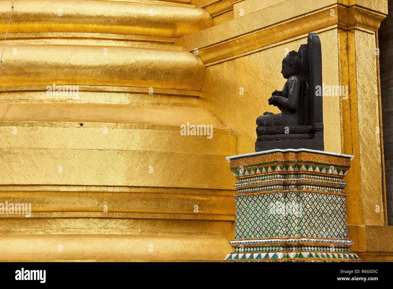 A small Buddha statue against a gilt column inside the Grand Palace in Bangkok, Thailand. Stock Photo