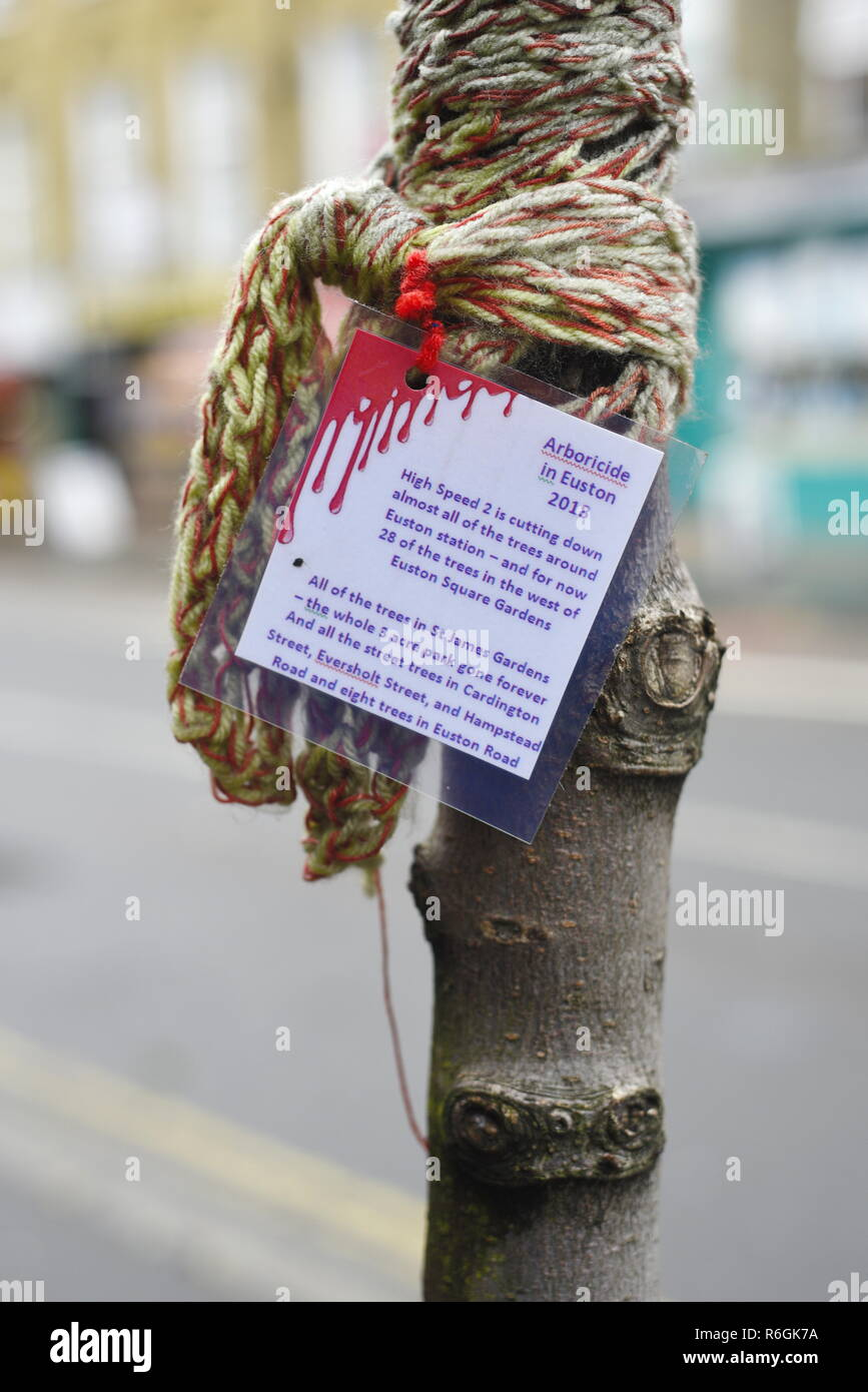 """Protest against the cutting down of trees with the HS2 High Speed 2 railway development plans. """"Arboricide in Euston 2018"""" - sign and wool knitting Stock Photo"""