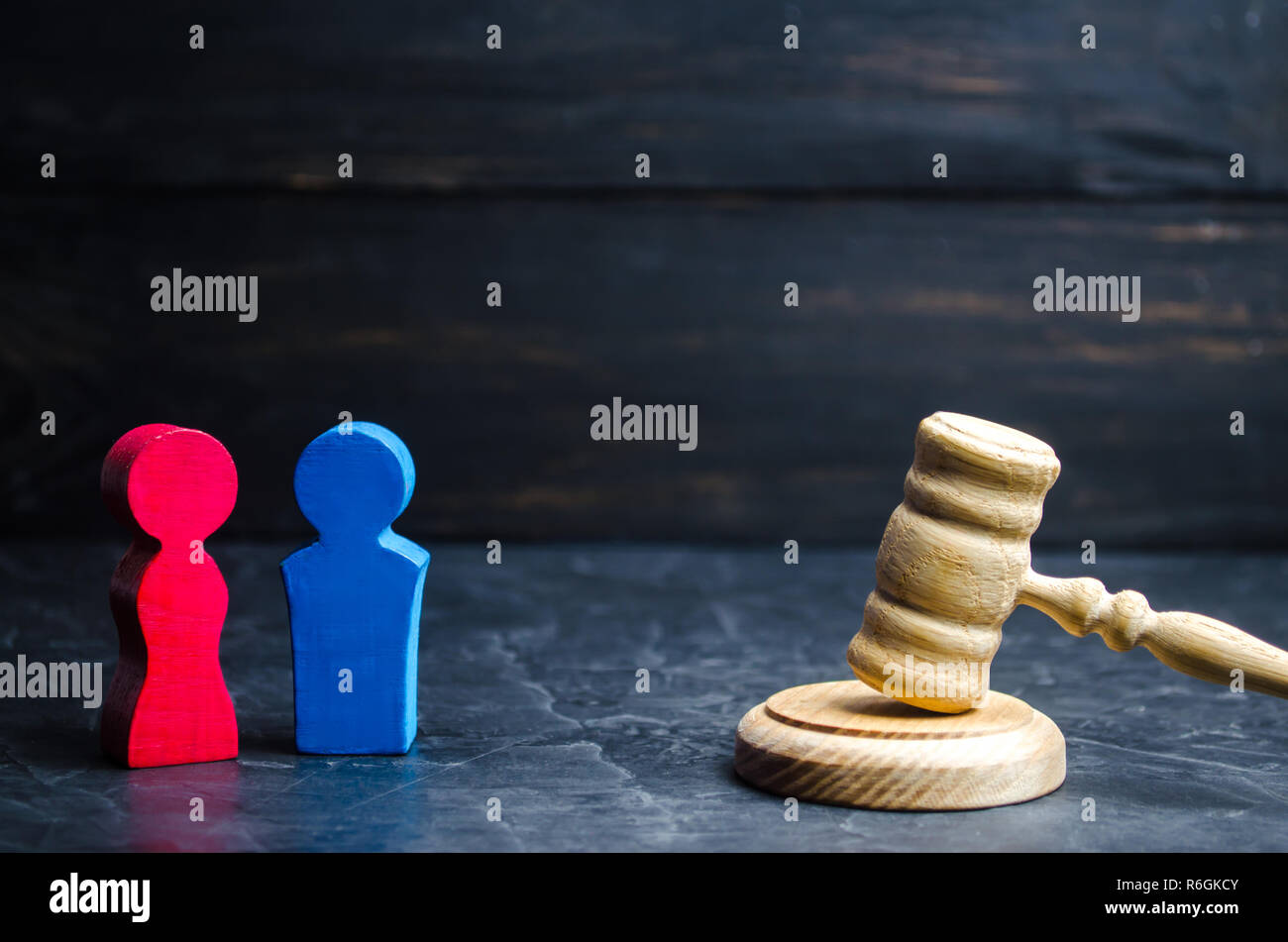 wooden figures of a man and a woman are standing near the judge's gavel. inequality concept : gender pay gap. divorce. Division of property in court.  - Stock Image