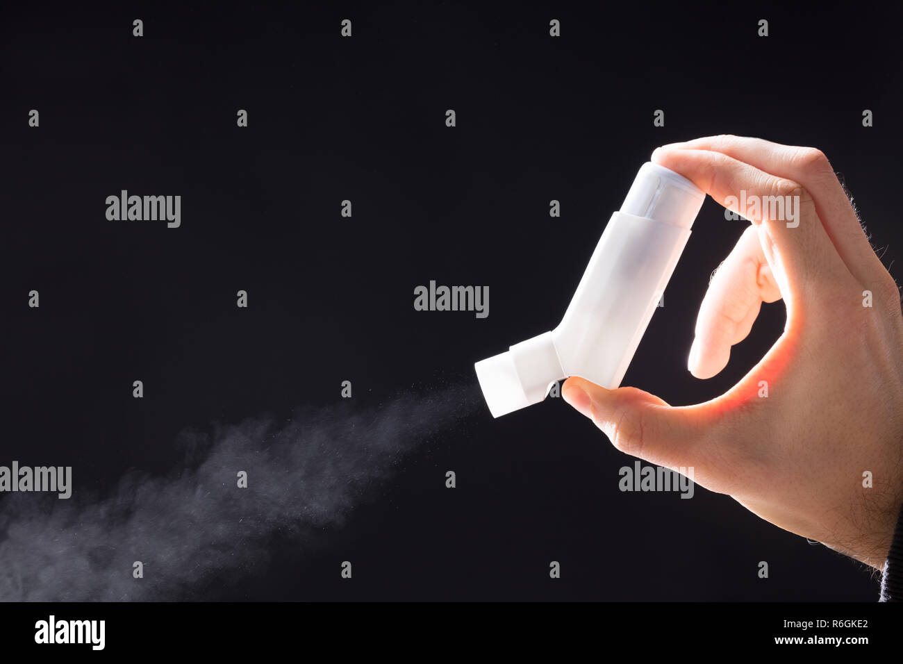 Person Using Asthma Inhaler - Stock Image