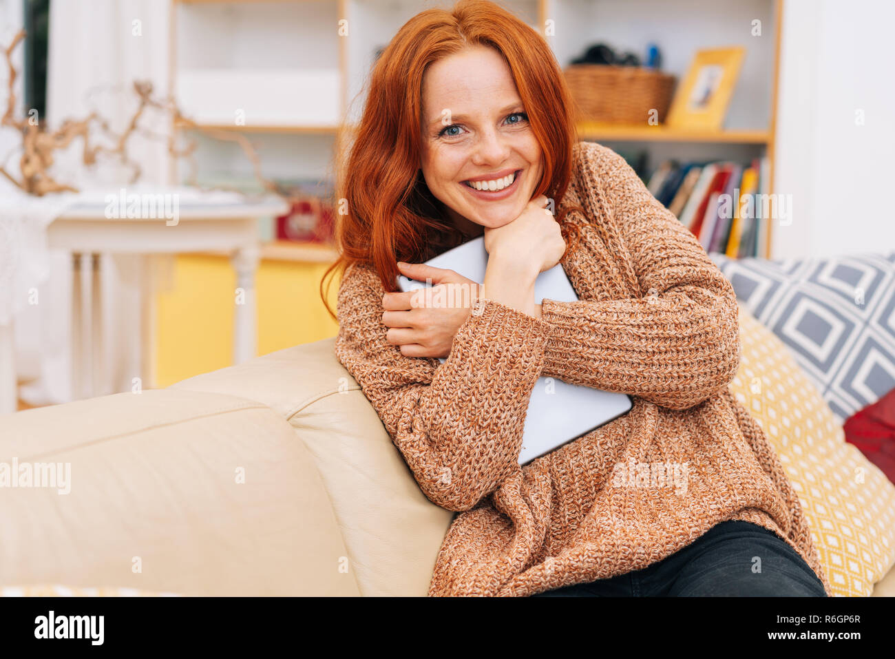 Vivacious friendly young woman clutching a tablet-pc to her chest as she grins at the camera while relaxing on an indoor sofa - Stock Image