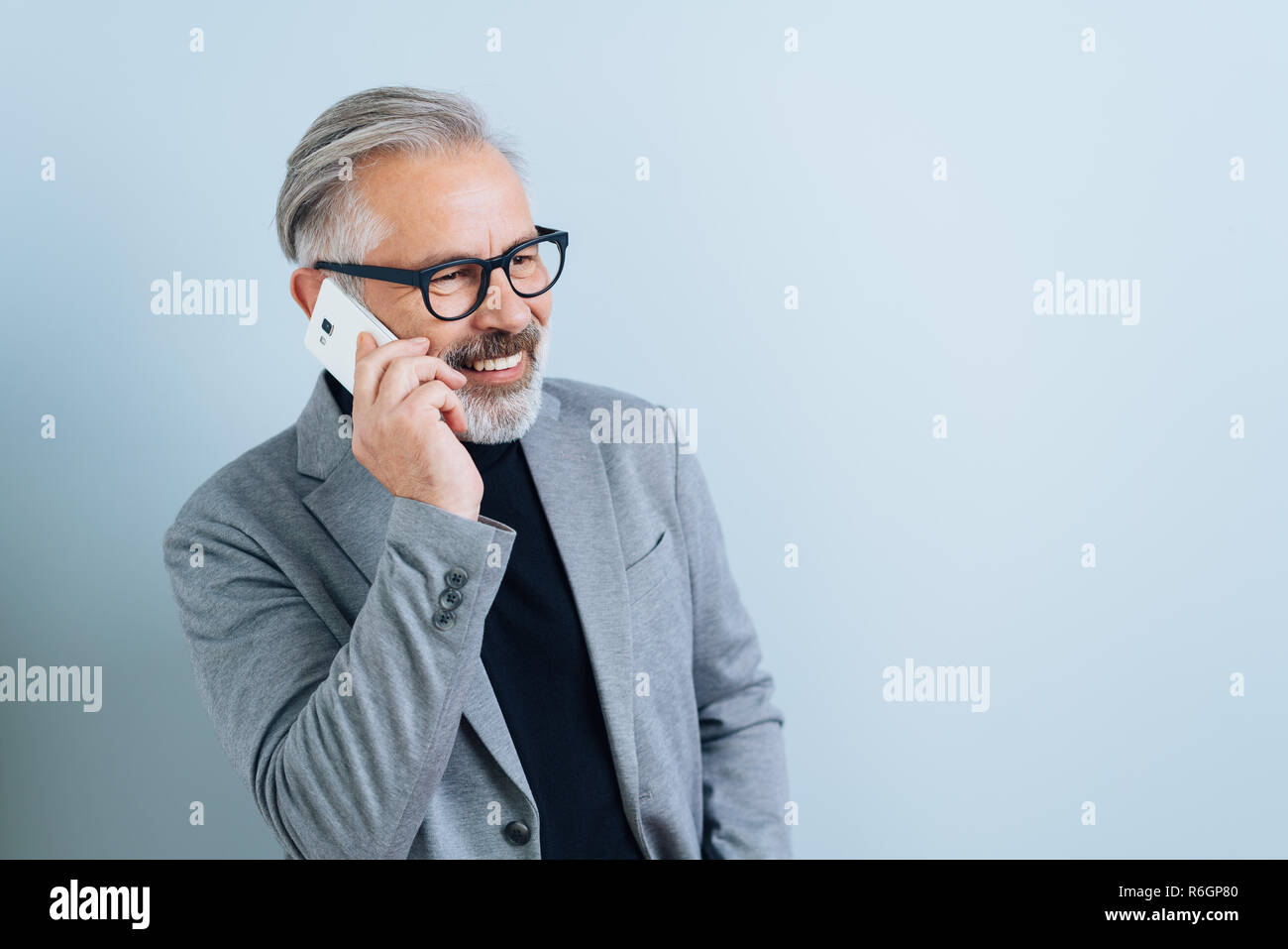 Businessman with greying beard and glasses standing smiling as he chats on a mobile phone against a white wall with copy space - Stock Image