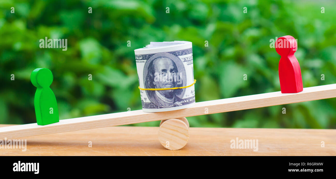 wooden figures of people on scales and dollars between them. a dispute between two businessmen. trial. debt restructuring. wage arrears. protection of - Stock Image