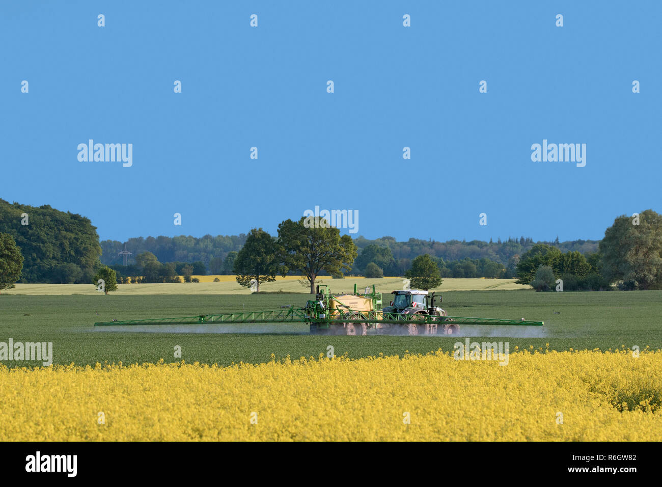 Farmer in tractor spraying herbicides / insecticides / pesticides over field with trailed sprayer in spring - Stock Image