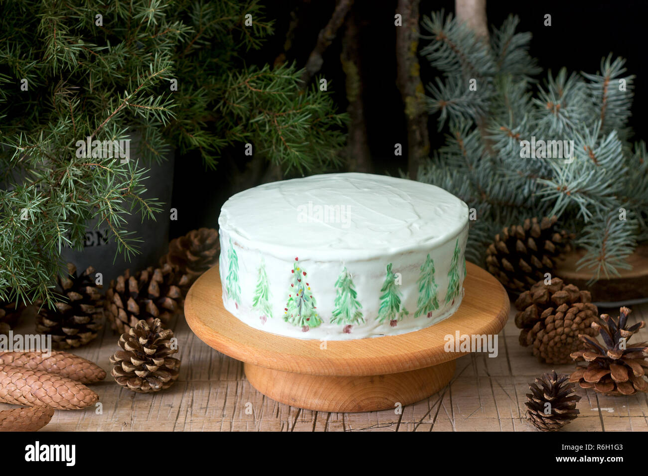 Celebratory Cake Decorated With Painted Christmas Trees On A Dark Background Of Branches And Cones Rustic Style Stock Photo Alamy