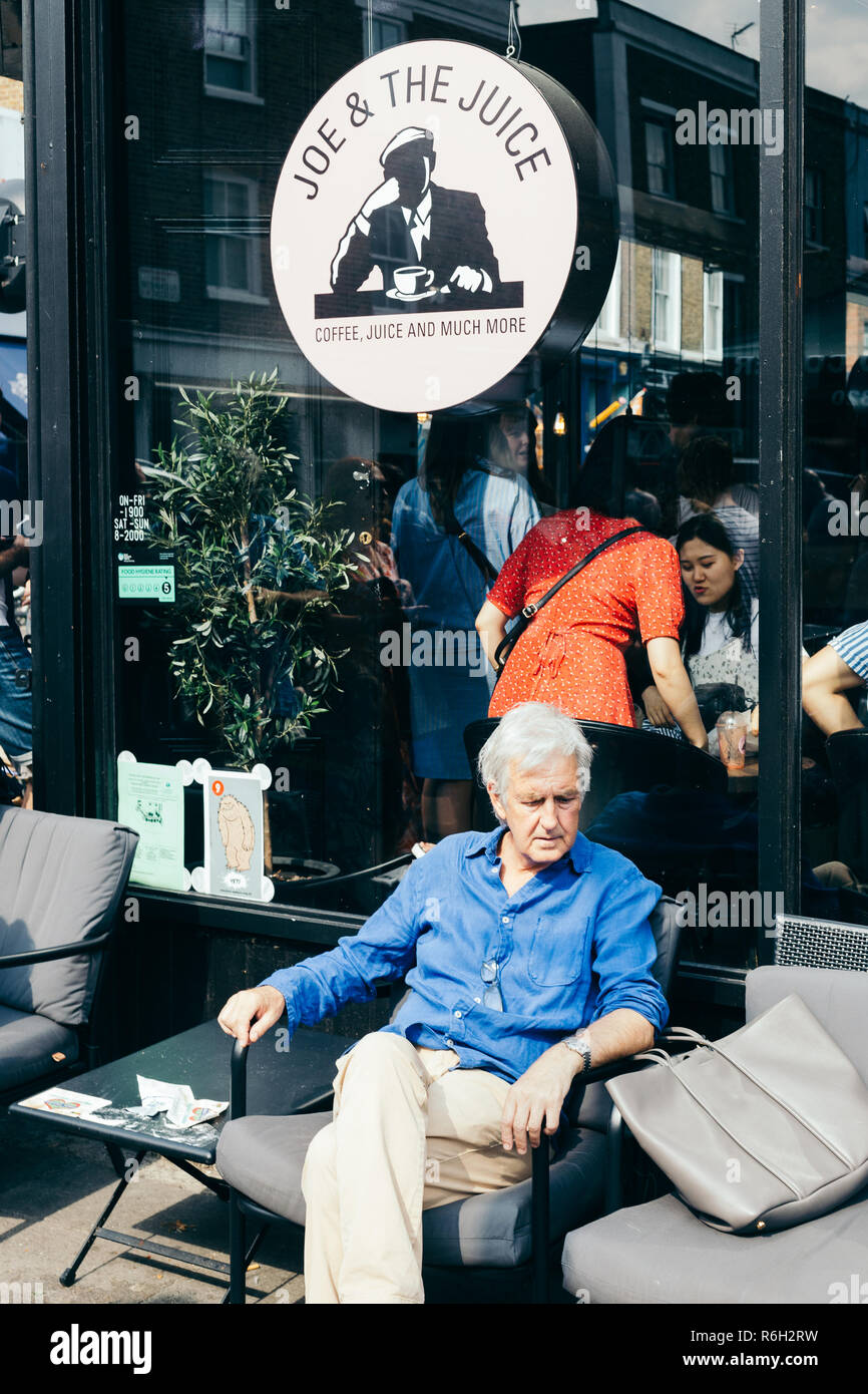 London/UK - July 20 2018: Elderly man resting in a chair in the street cafe in London - Stock Image