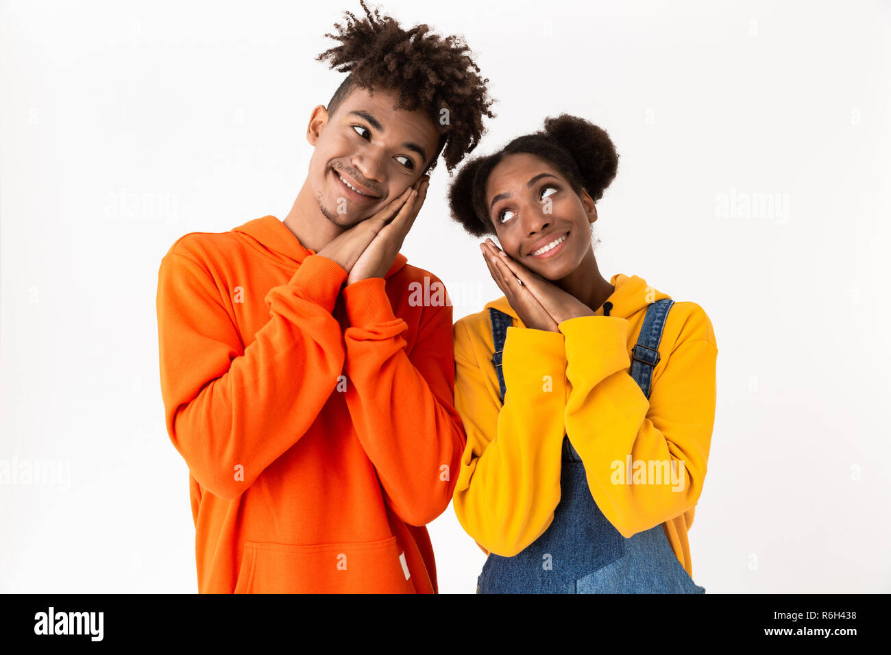 Image of affable african american couple in colorful clothes smiling at camera isolated over white background - Stock Image
