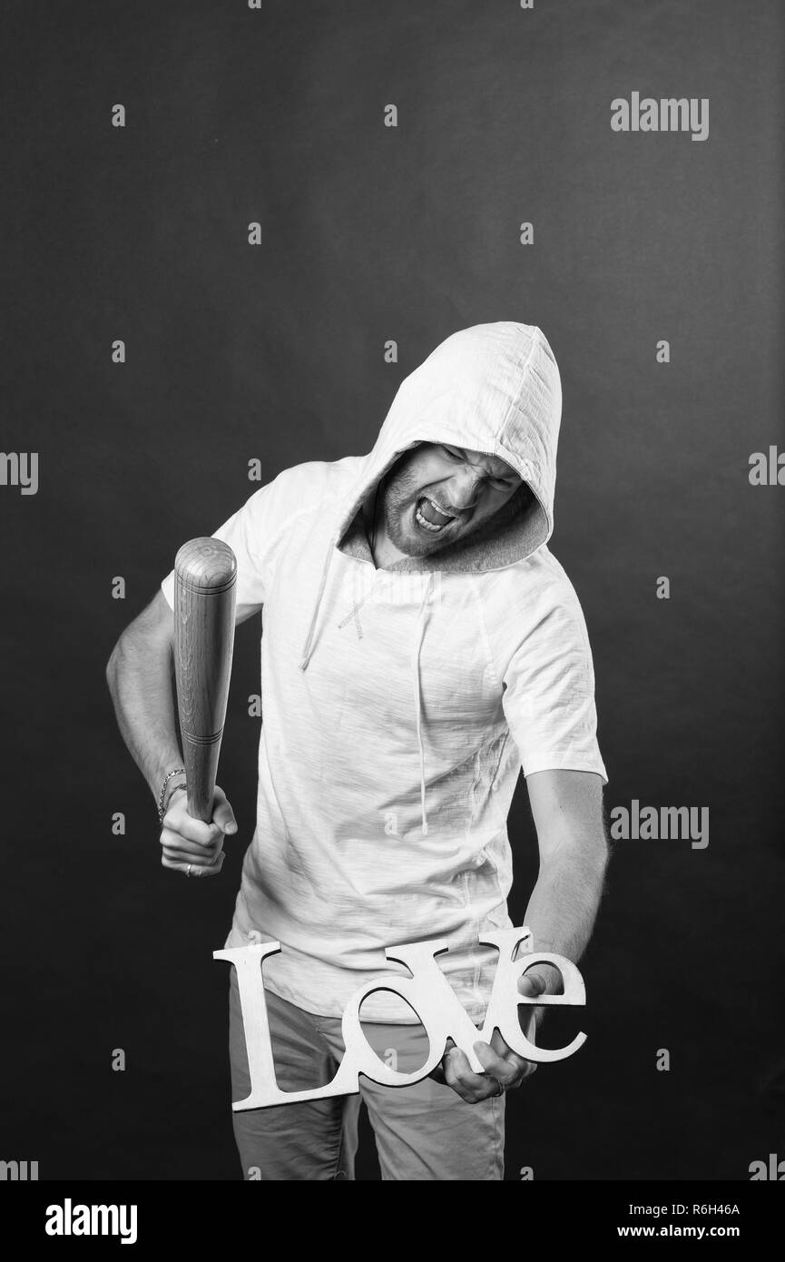 Man in hood bat love word. Angry hooligan with baseball bat. Divorce and break up. Anti valentines day. No love and hate concept. - Stock Image