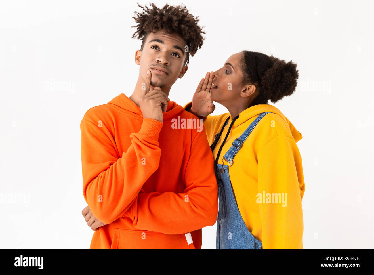 Photo of african american woman talking secrets in ear of her boyfriend isolated over white background - Stock Image