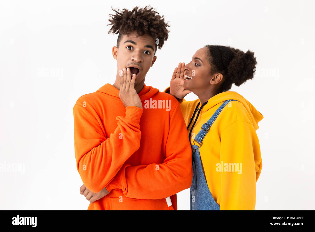 Photo of young african american woman talking secrets in ear of her brother isolated over white background - Stock Image
