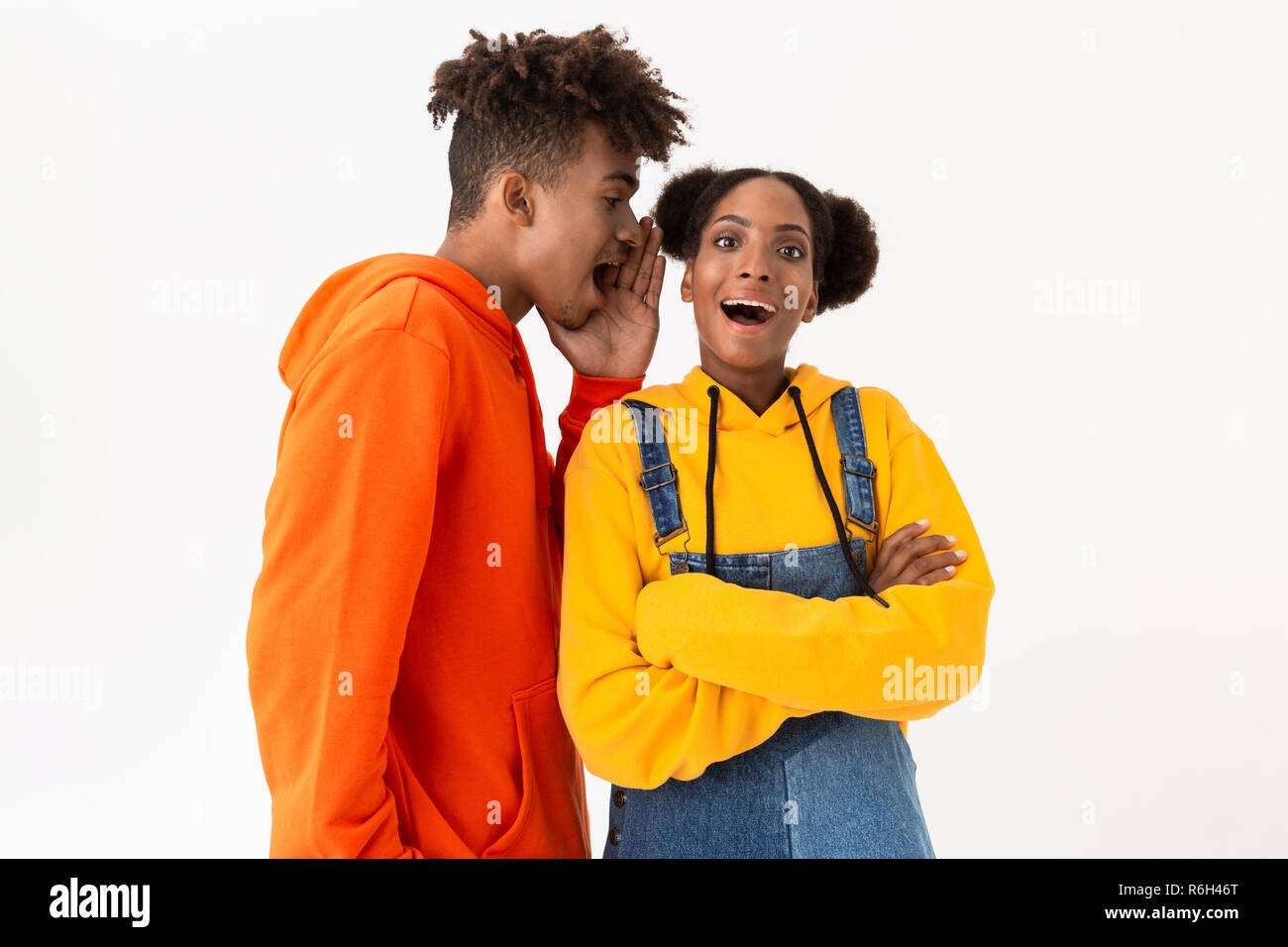 Photo of handsome african american man talking secrets in ear of his girlfriend isolated over white background - Stock Image