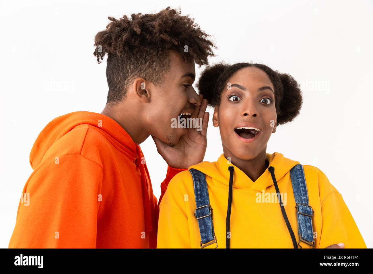 Photo of joyful african american man talking secrets in ear of his sister isolated over white background - Stock Image