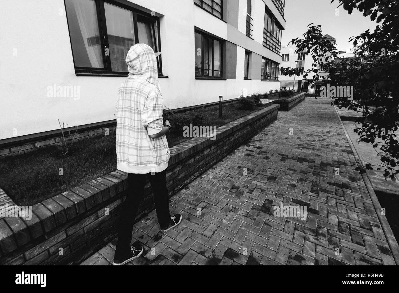 young man with beard in light checkered jacket with hood walking freely around city - Stock Image
