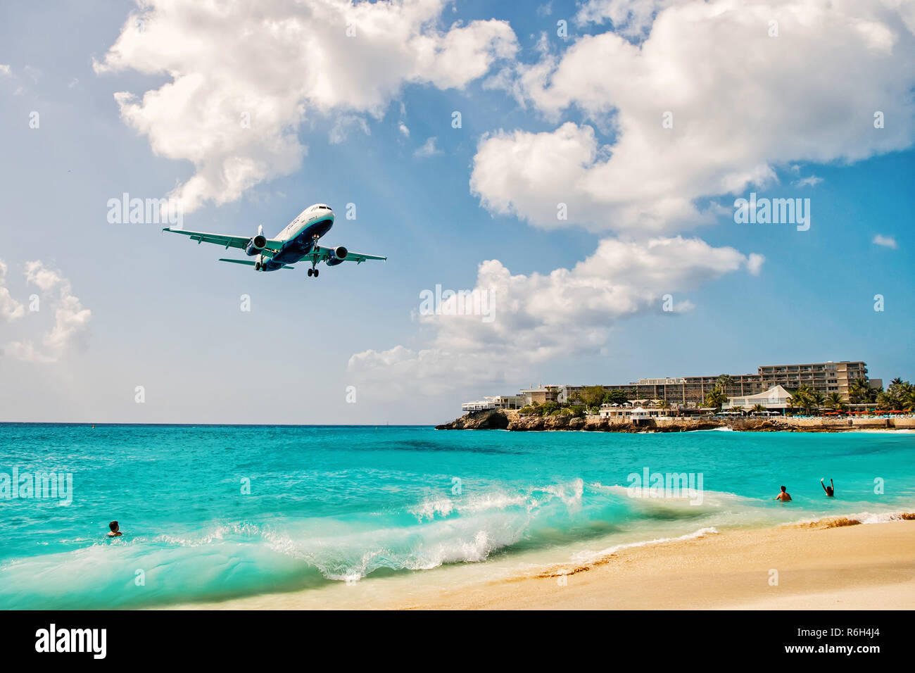 St.Maarten, Kingdom of Netherlands - February 13, 2016: beach crowds observe low flying airplanes landing near Maho Beach on island of St.Maarten in the Caribbean - Stock Image