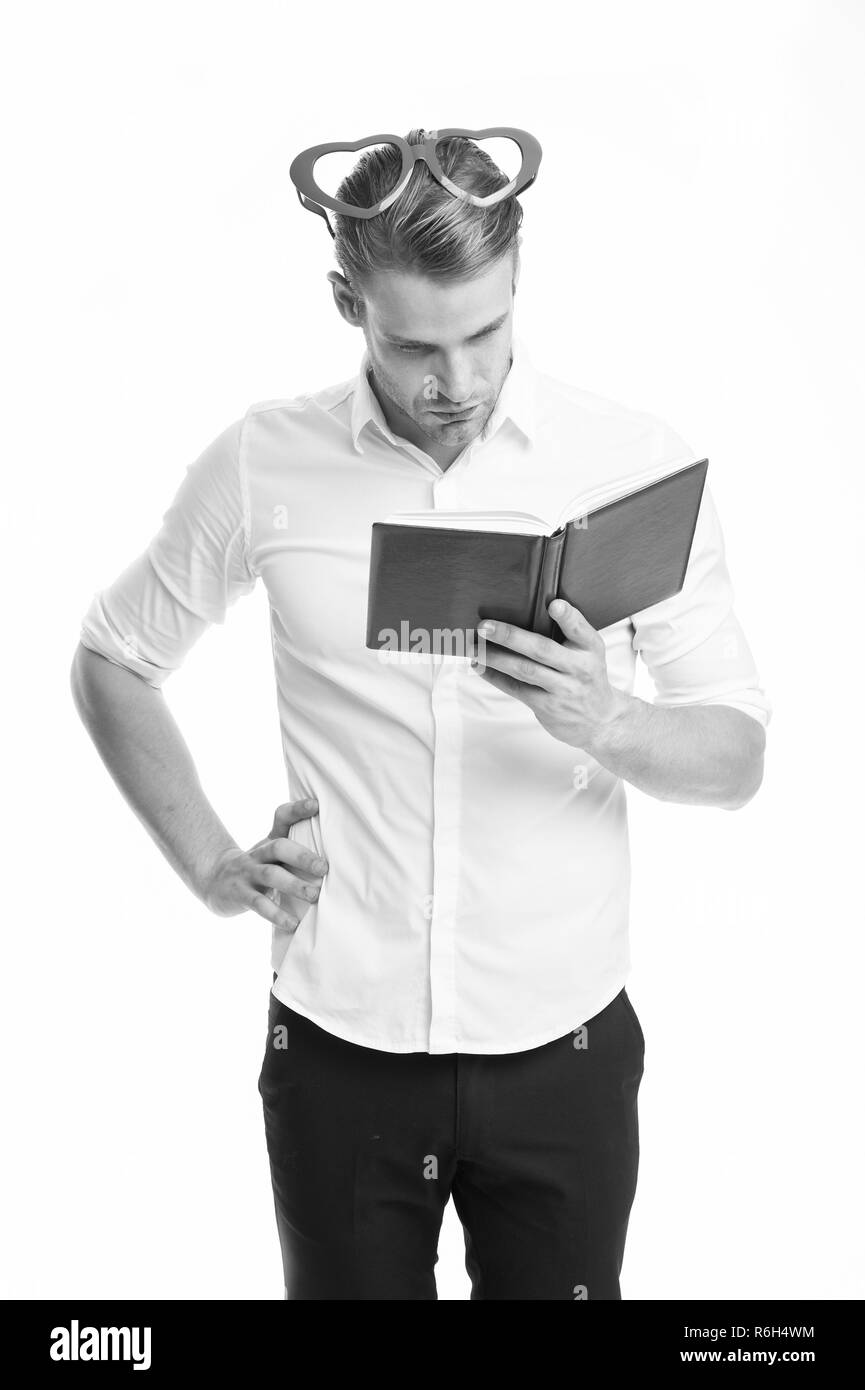 Reading poetry. Man handsome young searching nice poetry. Man busy face in heart shaped eyeglasses reading book. Guy found poetry in book isolated white background. Reading book concentrated. Stock Photo