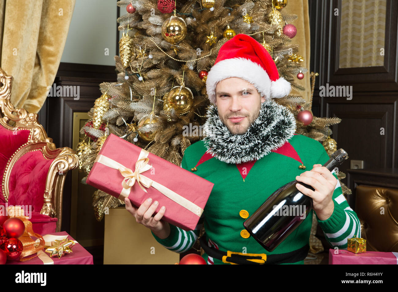 Hope this season finds you all wrapped up in happy. Happy man with new year gift box. Guy is celebrating new year at home. Merry Christmas and Happy New Year. Man in santa hat hold new year present. - Stock Image
