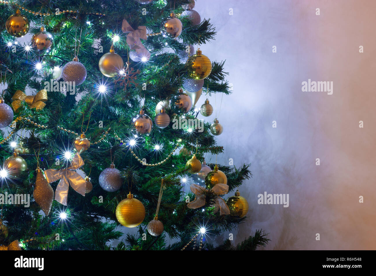 A Green Fir Christmas Tree With White Lights And Silver And Gold Decorations Against A White Background Stock Photo Alamy