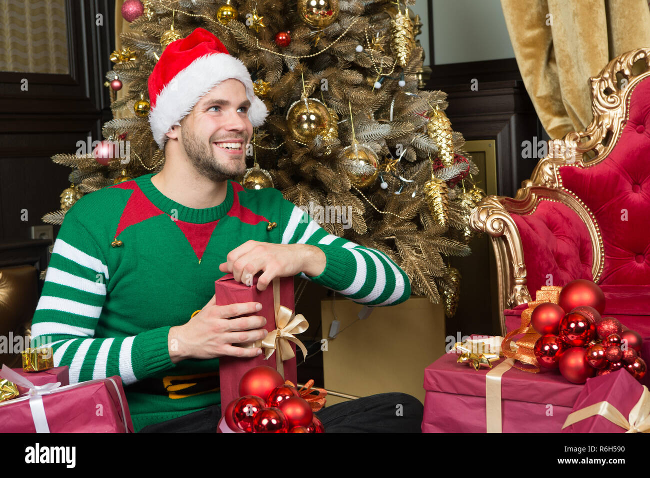 Opening Christmas present. Guy is celebrating Christmas at home. Man in santa hat hold Christmas presents. Happy man with xmas gift boxes. Delivery Christmas gifts. Indulge yourself in joy. Stock Photo
