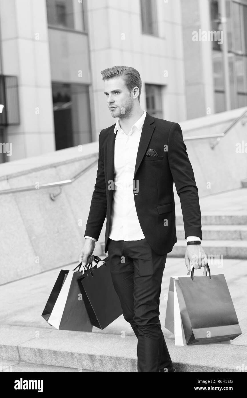 Man carry shopping bags on urban backdrop. Businessman with package walk in street. Fashion shopper with paperbags. Great day for shopping. Big sale on black friday. Man bought many birthday presents - Stock Image
