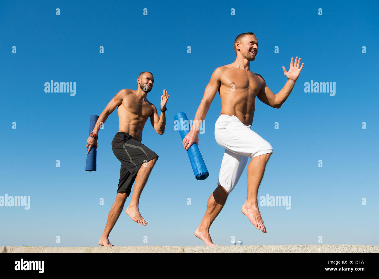 Forward to healthy lifestyle. Men with yoga mat captured in motion blue sky background. Sportsman with mat running. Run training outdoor. Runners hurry to stretch muscles after training. Yoga classes. - Stock Image