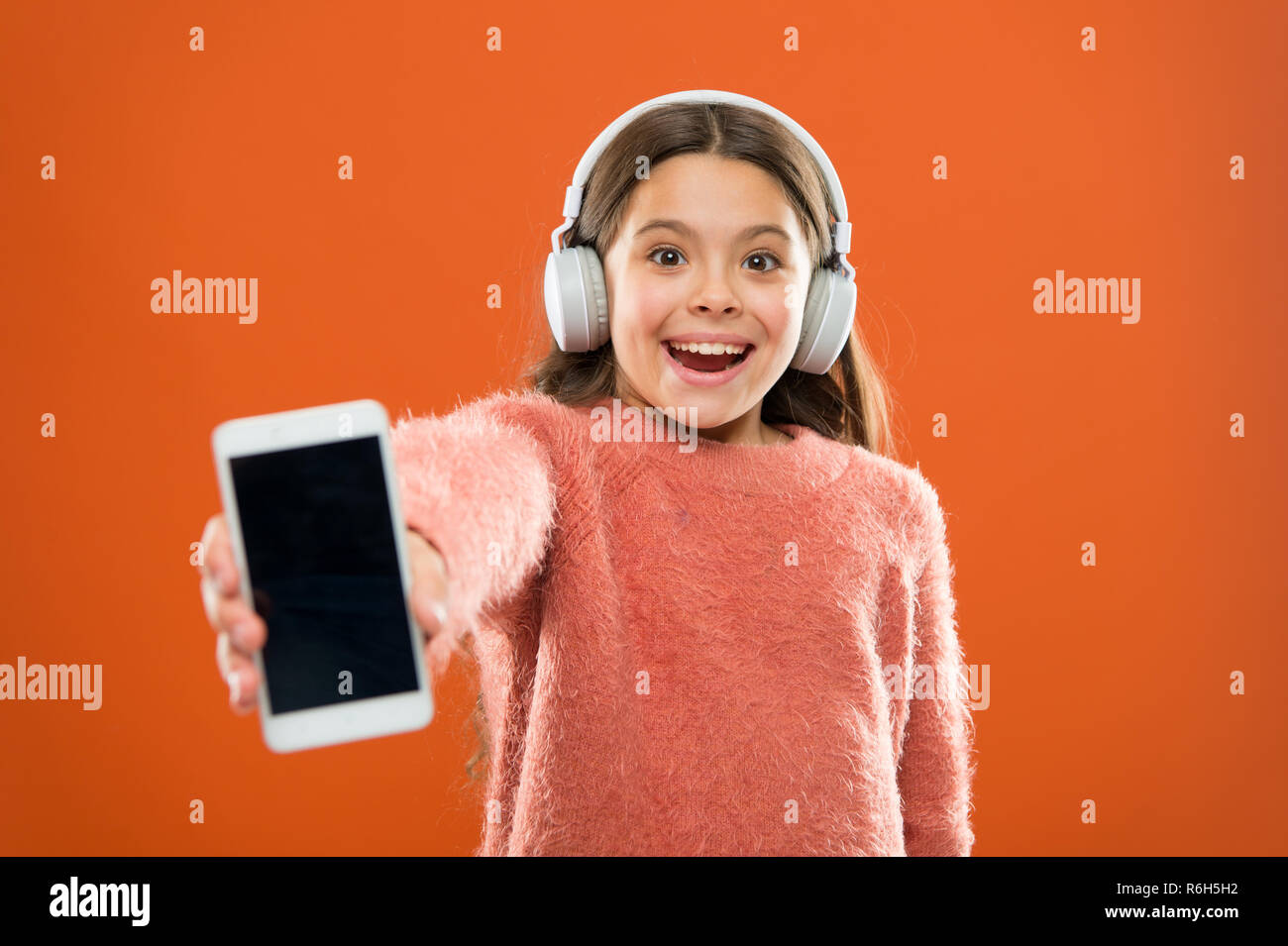Get music family subscription. Access to millions of songs. Enjoy music concept. Best music apps that deserve a listen. Girl child listen music modern headphones and smartphone. Listen for free. - Stock Image