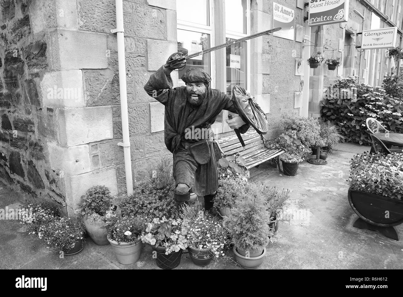 Oban, United Kingdom - February 20, 2010: warrior statue on building corner with pot plants. Town house with bench and flowers in yard. Victorian style architecture and design. Hotel accommodation. - Stock Image