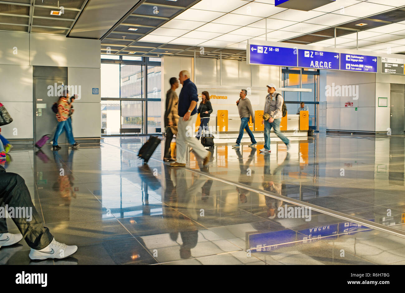 Frankfurt am Main, Germany - October 11, 2015: hurry people tourists with travel suitcase or bag luggage in airport or station terminal walks as blurred or defocused background in speed motion. traveling and business - Stock Image