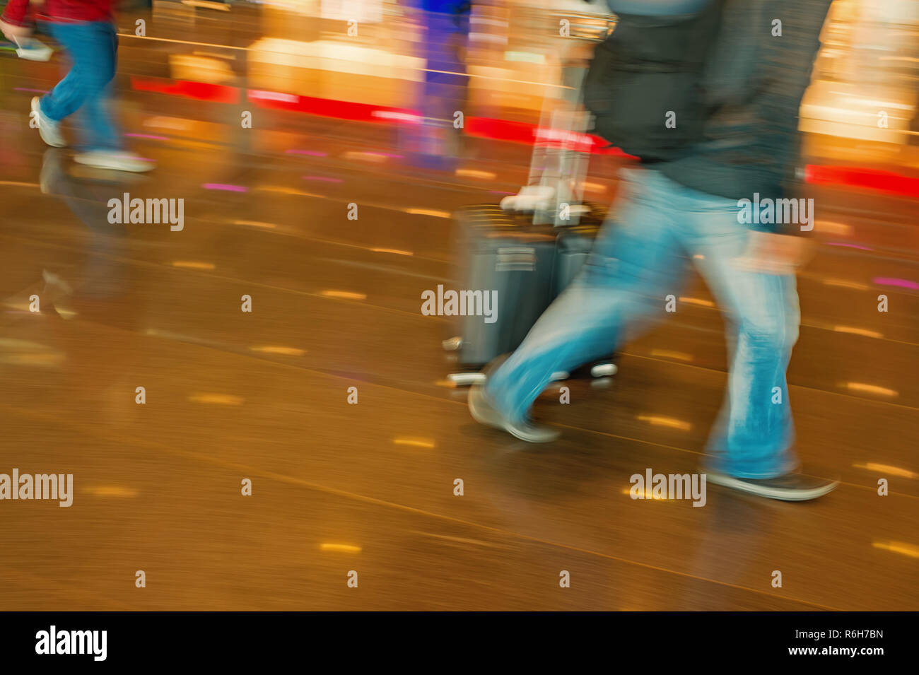 hurry people tourists with travel suitcase or bag luggage in airport or station as blurred or defocused background in speed motion - Stock Image