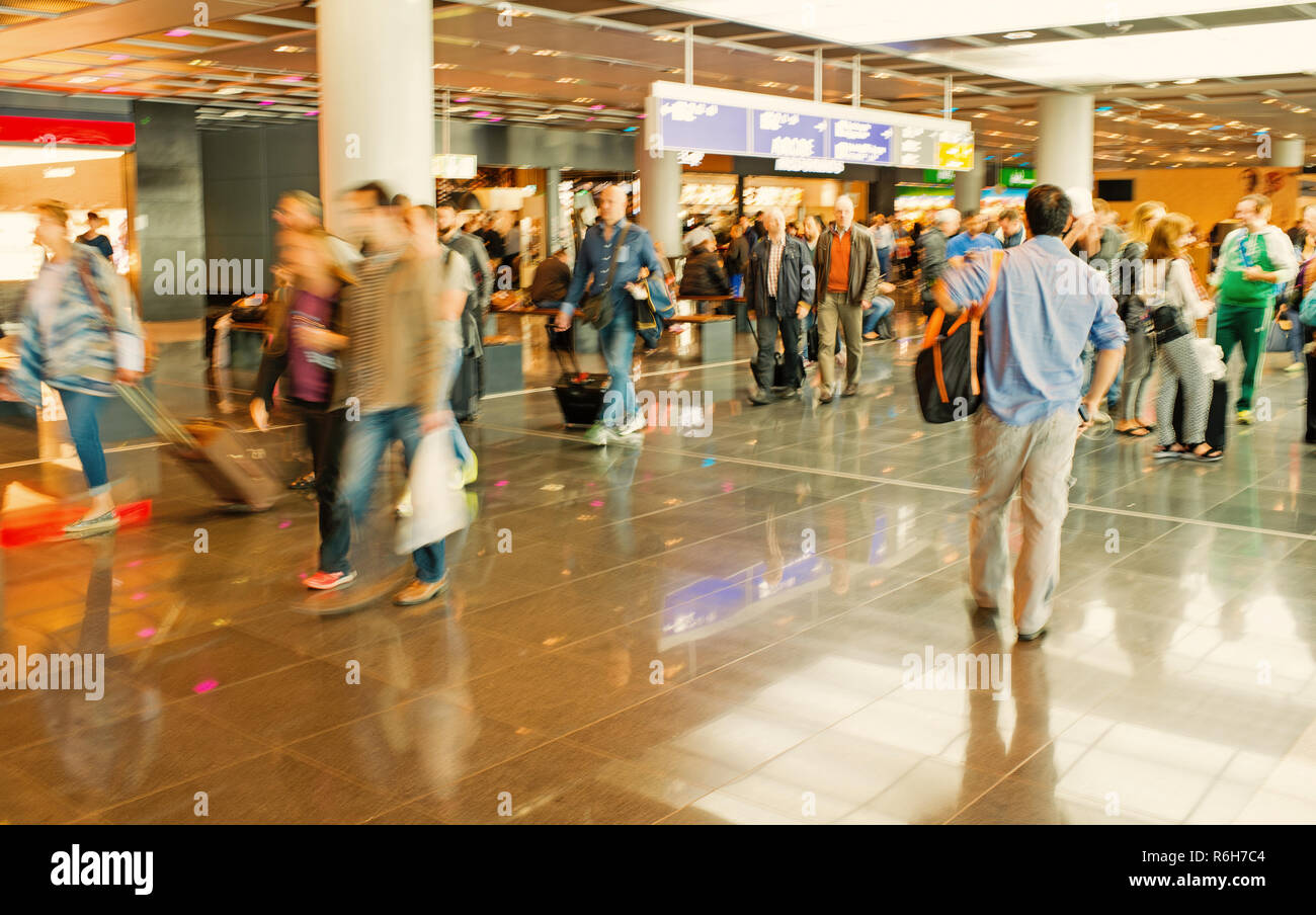 hurry people, tourists crowd with travel suitcase or bag luggage in airport or station terminal walks as blurred or defocused background in speed motion. traveling and business - Stock Image