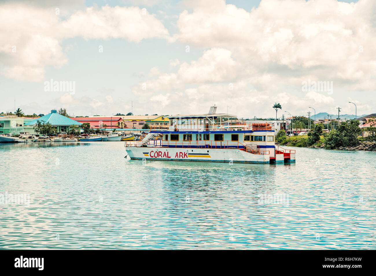 St. John, Antigua - March 05, 2016: excursion boat, white passenger ship, Coral Ark touristic vehicle at moorage in sea port, bay with motorboats on water summer day on blue cloudy sky - Stock Image