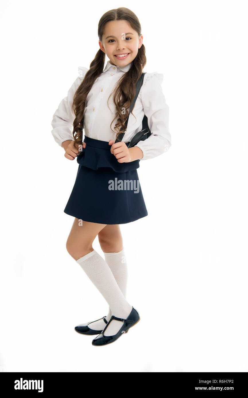 Learn how fit backpack correctly for school. Schoolgirl cute in formal uniform wear backpack. School backpack concept. Right and wrong ways to wear backpack to prevent pain and keep proper posture. - Stock Image
