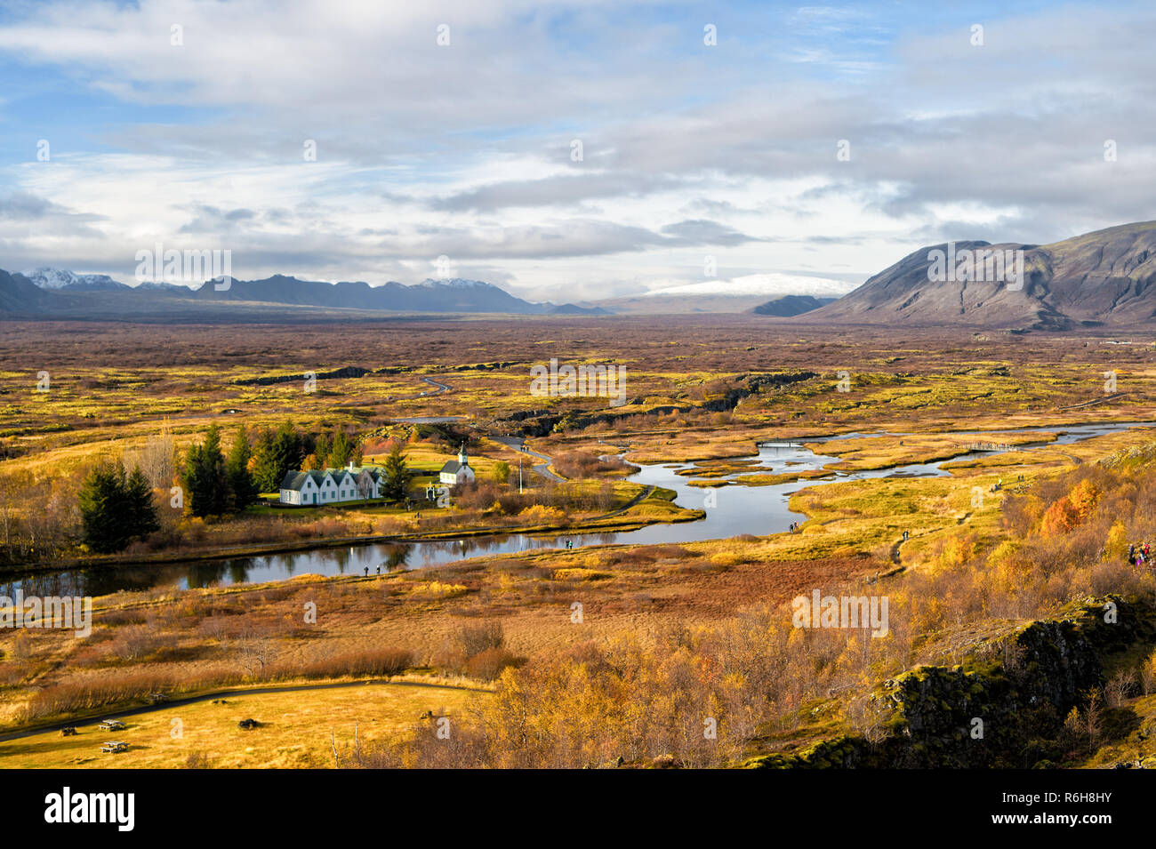 Haukadalur valley in Iceland. Beautiful landscape with river in valley. Little buildings in peaceful nature environment. Valley landscape sunny autumn day cloudy sky. Amazing beauty of valley. Stock Photo