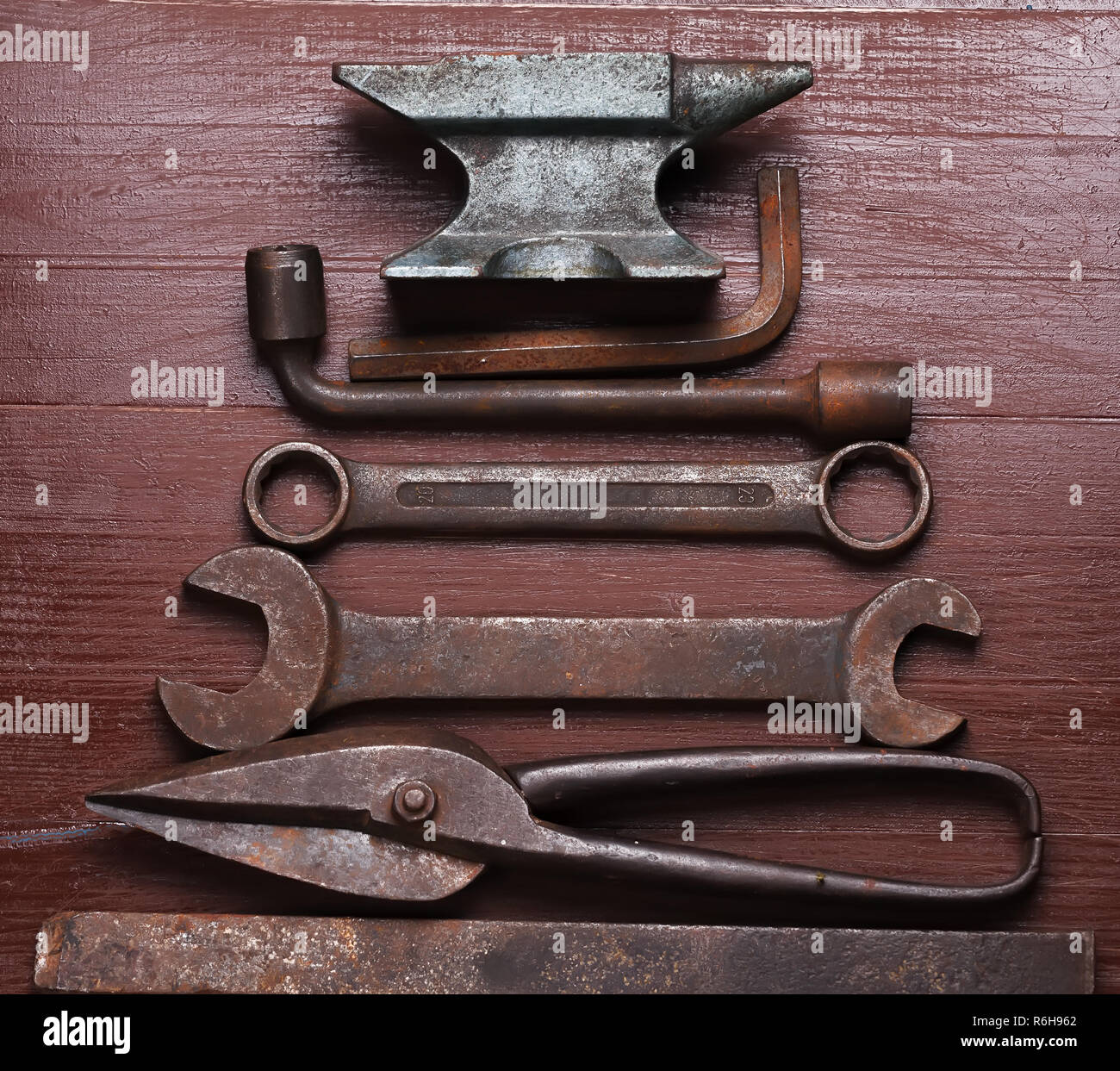 Old rusty rugged anvil and other blacksmith tools on brown natural