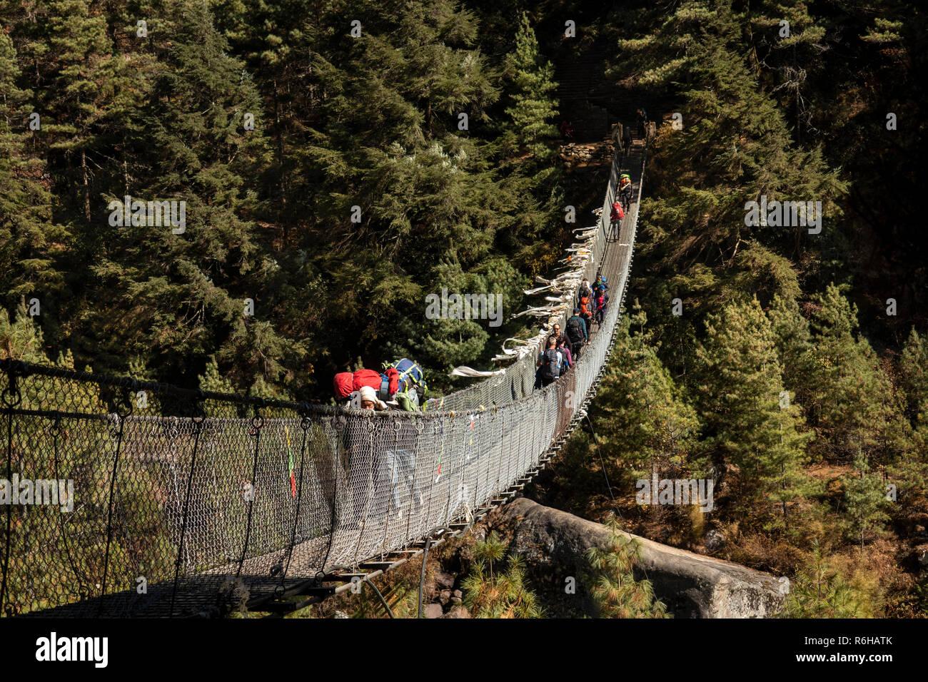 Nepal, Jorsale (Thumbug), line of people crossing metal suspension bridge over Dudh Khosi river - Stock Image