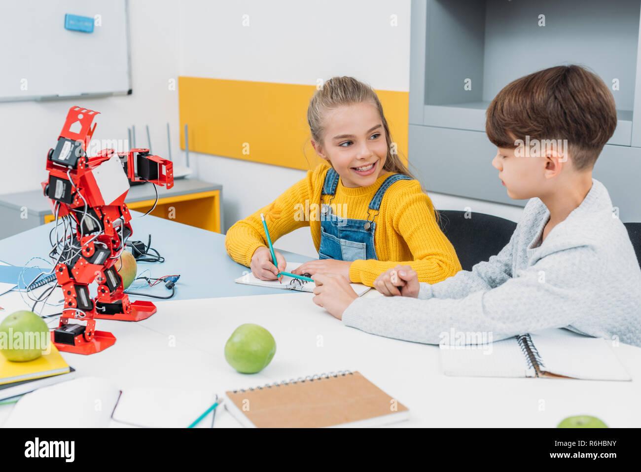 cheerful schoolchildren talking at STEM robotics lesson - Stock Image