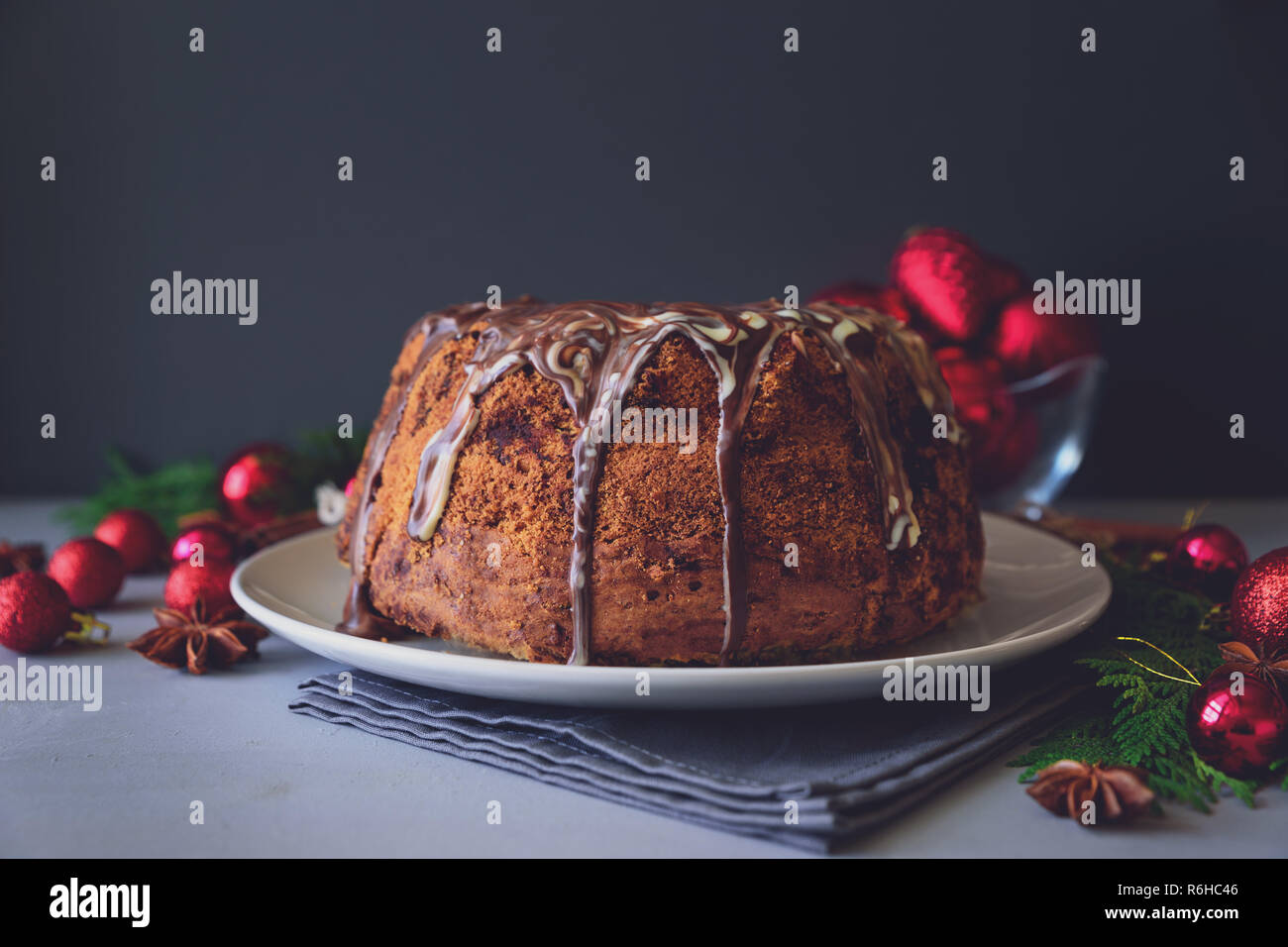 Christmas cake with chocolate icing on gray wooden background. Holiday decorations concept. Top view. Flat lay. Copy space. Toned Stock Photo