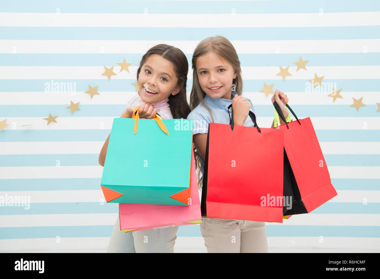 Obsessed with shopping and clothing malls. Discount concept. Kids cute girls hold shopping bags. Shopping discount season. Spending great time together. Children satisfied shopping striped background. - Stock Image