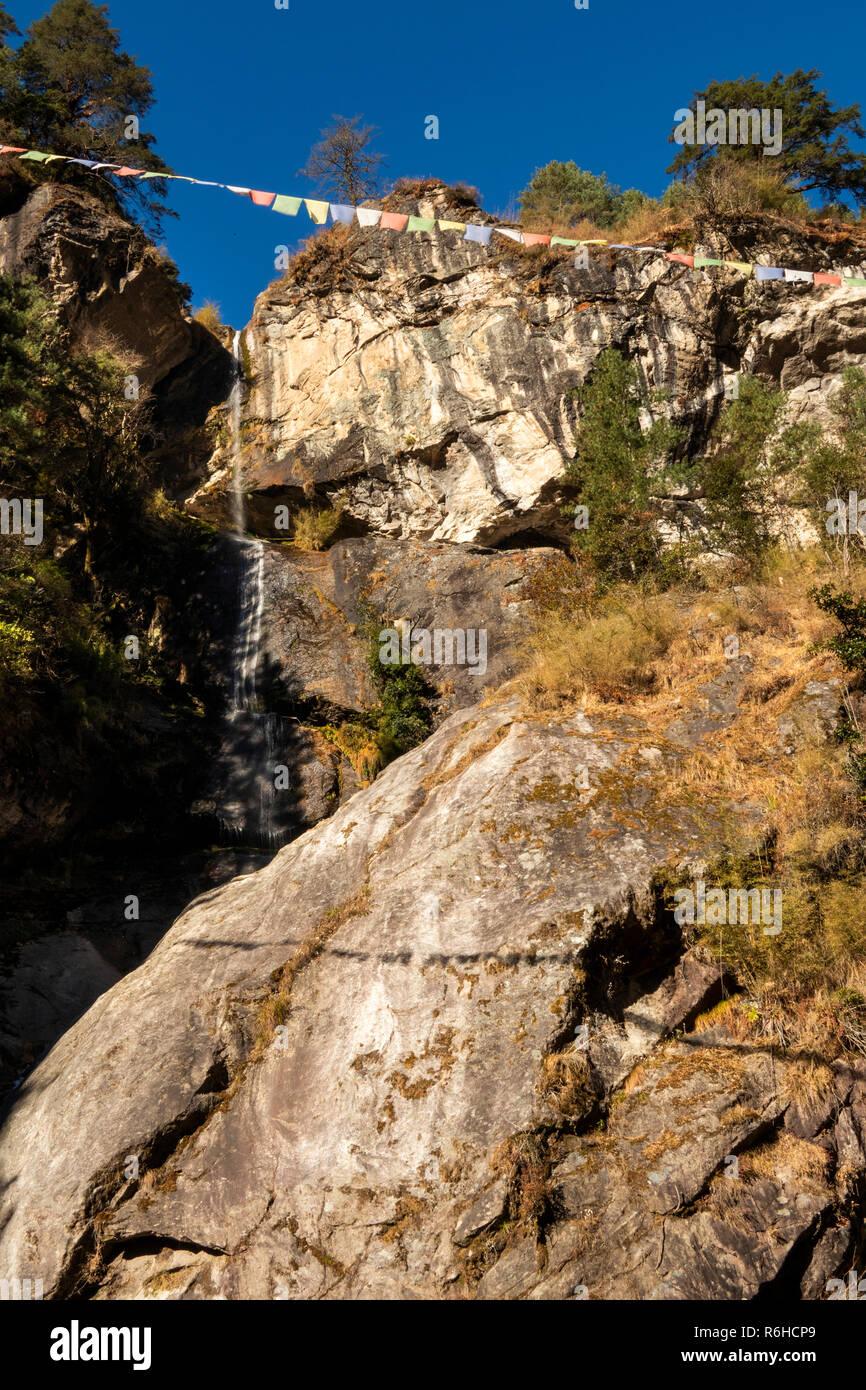 Nepal, Phakding, Buddhist prayer flags above waterfall feeding Dudh Kosi River - Stock Image
