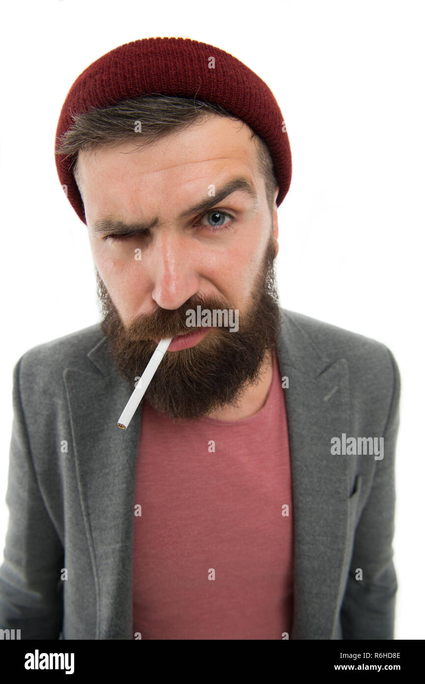 Brutal unshaven guy smoking white background close up. Man brutal bearded hipster smoking cigarette. Brutal habits and lifestyle. Hipster brutal bearded tobacco smoker. Brutality and masculinity. - Stock Image