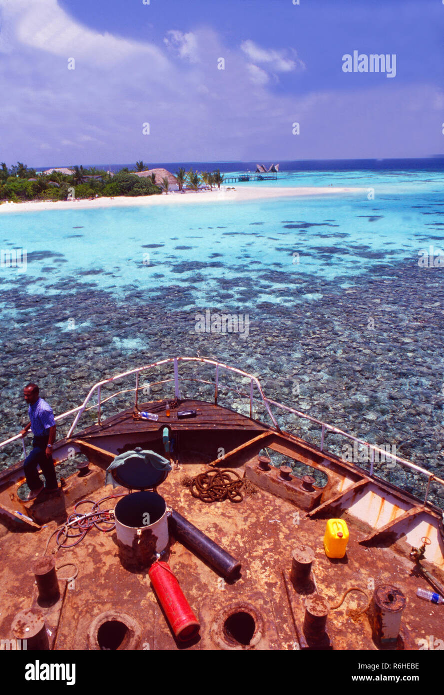 Maledives: Local people pulling a old freight ship to the coast to sink it and cultivate a coral reef - Stock Image