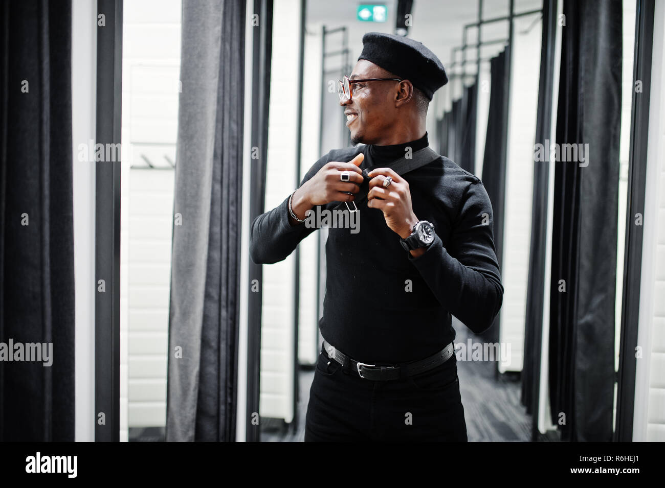 e33b999daaf6a Stylish casual african american man at black outfit and beret with waist  bag at fitting room clothes store