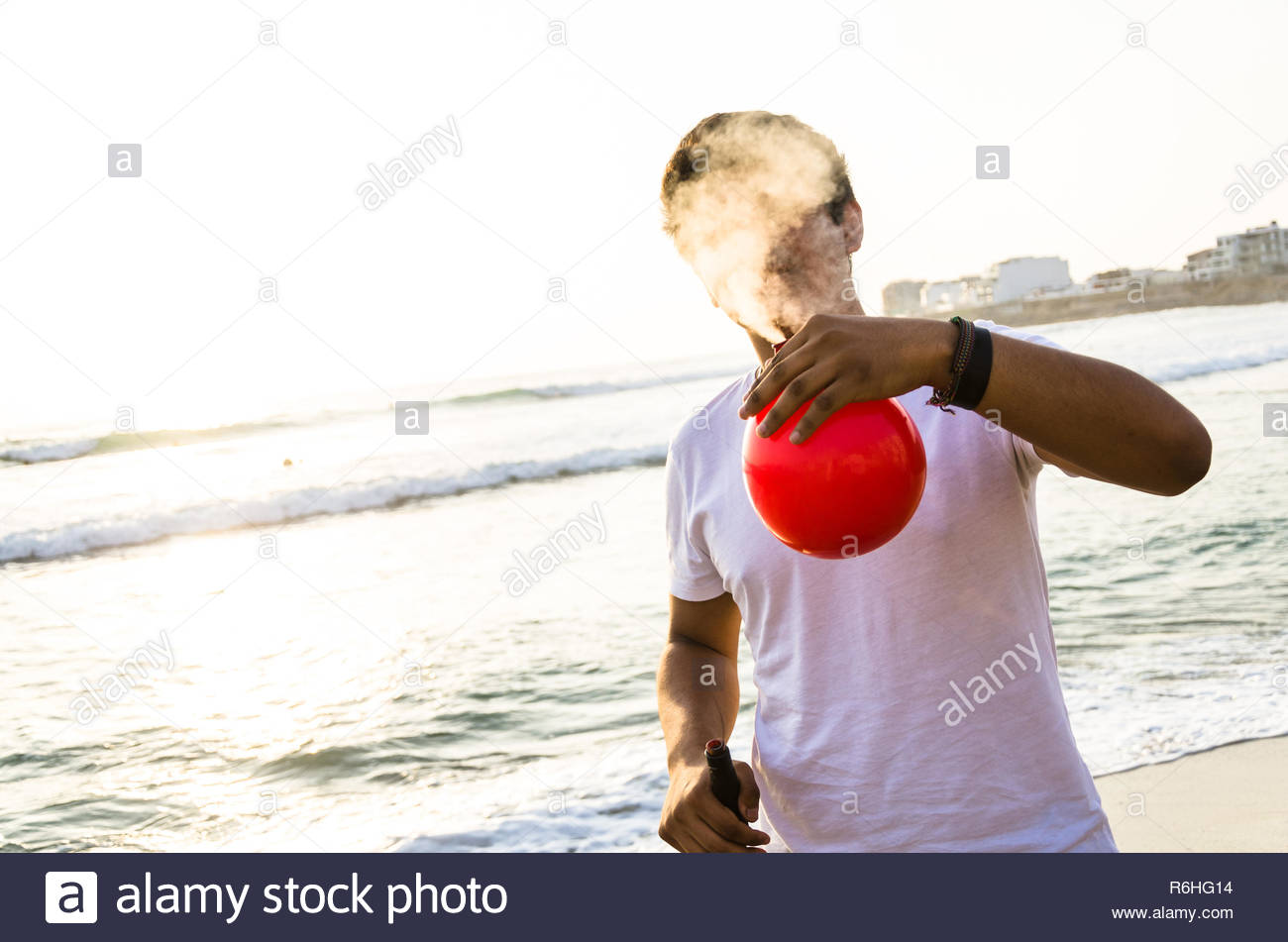 Young man with electronic cigar and a red balloon on the beach - Stock Image