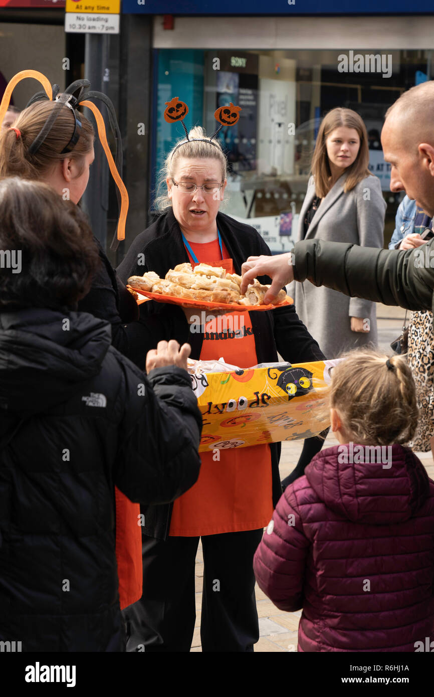 Shop staff offering free samples of Sausage Rolls to shoppers in Leeds,West Yorkshire,England,UK. - Stock Image
