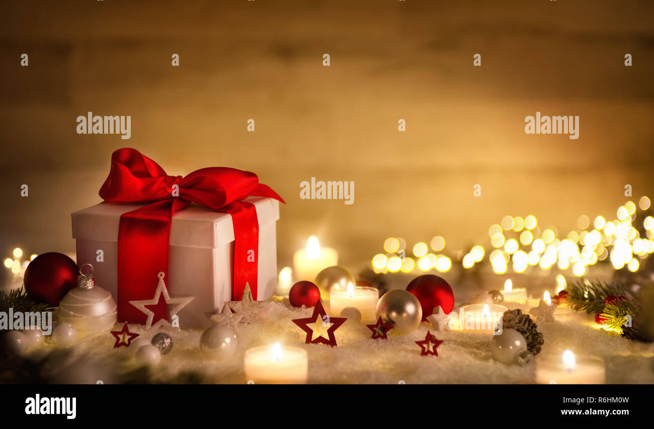 Christmas scene with a white gift box, red bow, candles, lights, baubles and snow, with brown copy space - Stock Image