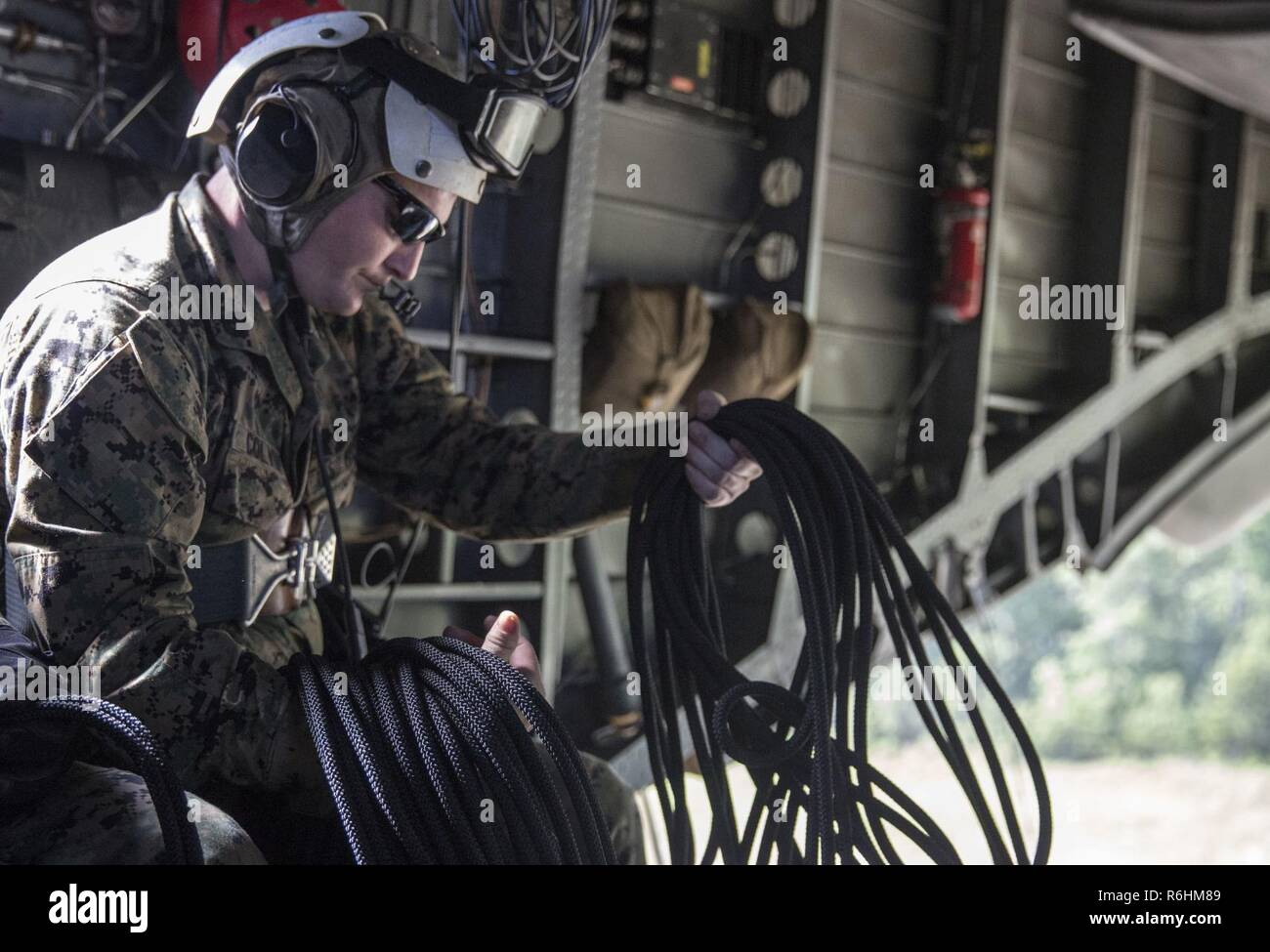 Staff Sgt. Jerry Colvin unravels a rope before rappelling out of a CH-53 Super Stallion during a ceremony at Stone Bay, a Camp Lejeune satellite training area, N.C., May 17, 2017.  The ceremony marks the reopening of Landing Zone Vulture, which closed Sept. 2, 2015 after a CH-53 crashed resulting in the death of one Marine.  The instructors took the opportunity to memorialize their fallen Marine, Staff Sgt. Jonathan Lewis, through the sustainment rappel. Staff Sgt. Colvin is with EOTG, II Marine Expeditionary Force Headquarters Group. - Stock Image