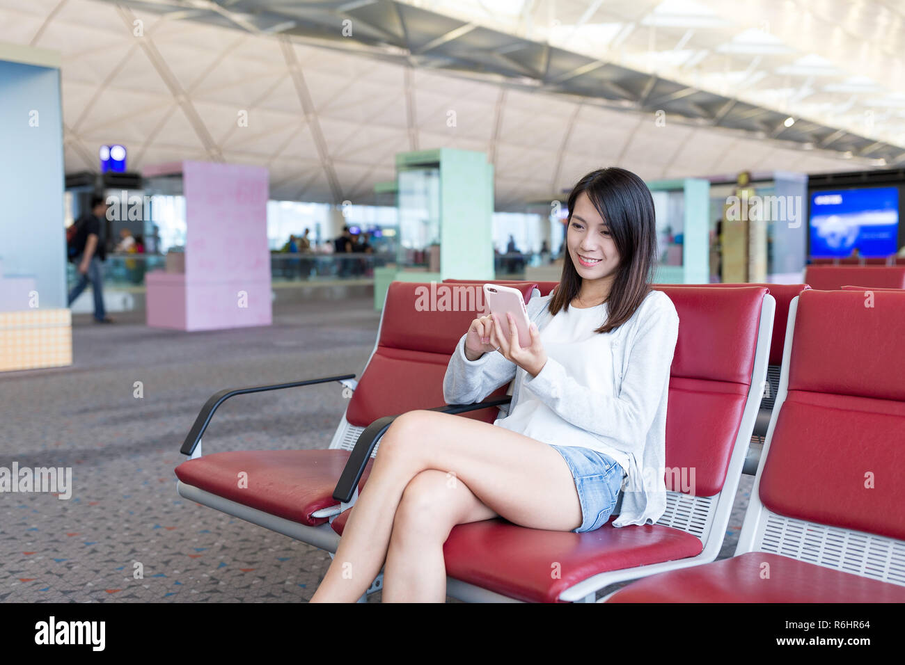 Woman using mobile phone in the airport - Stock Image