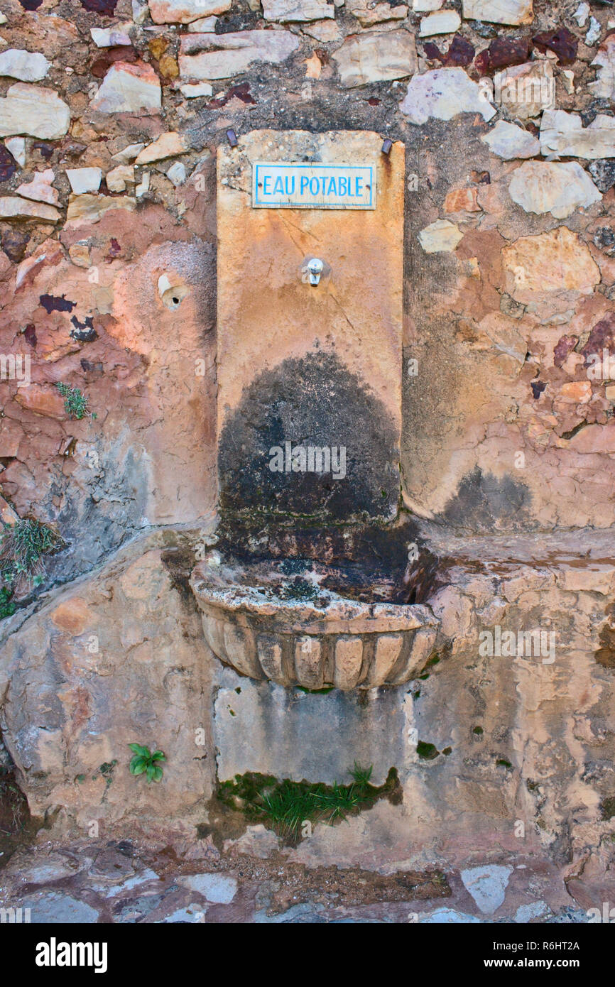 Old drinking water fountain in southern France with a blue sign saying 'drinking water' in French. Stock Photo