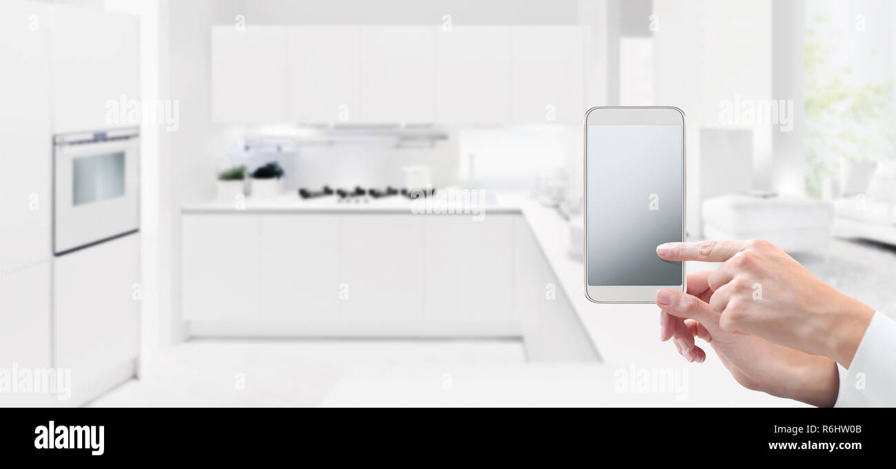 smart home automation control concept hand touch cell phone screen on kitchen background web banner and copy space template Stock Photo
