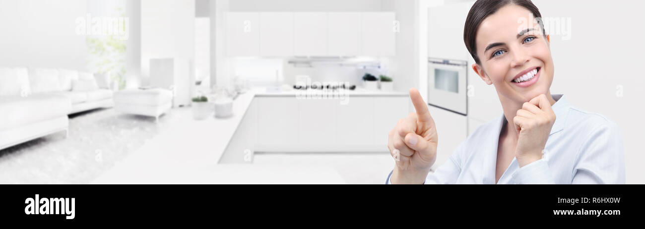 smart home automation smiling woman hand touch screen on kitchen and living room background web banner and copy space template Stock Photo